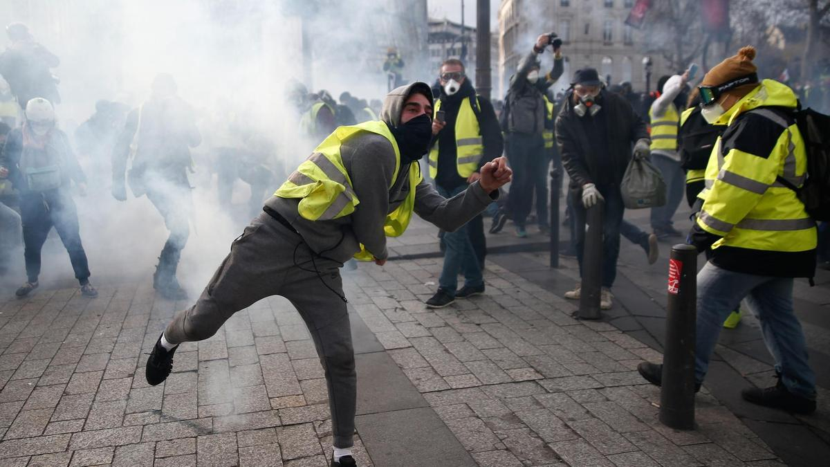 A protestor wearing a yellow vest (gilet jaune) throws a tear gas canister back at police during a protest in Paris