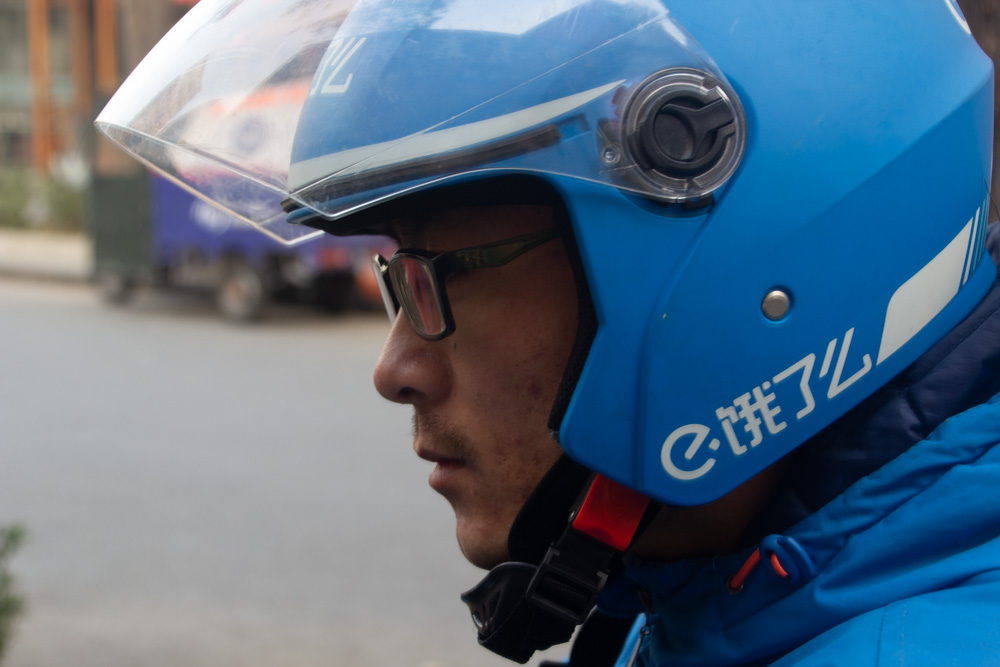 Chinese food delivery worker in a helmet