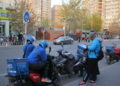 food delivery workers on a road in Beijing