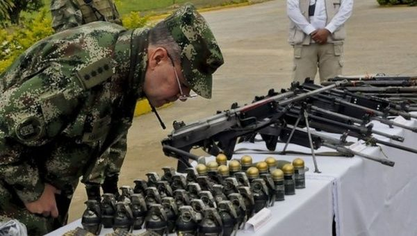 Colombian army officers examines seized grenades and weapons from the FARC in July, 2013