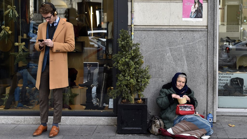 A man looks at a mobile phone beside a woman begging on the pavement in Madrid on December 15, 2015