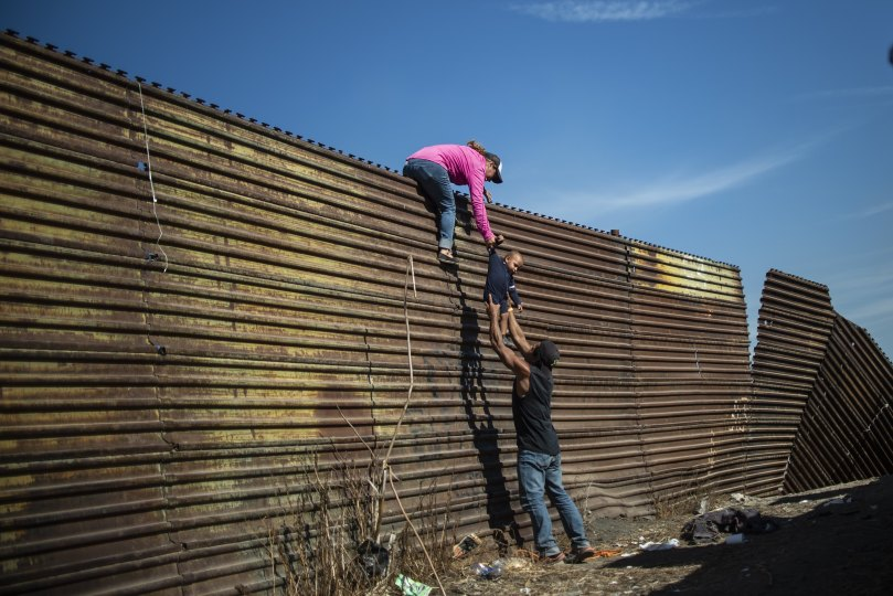 Central American migrants climb the border fence between Mexico and the United States, near El Chaparral border crossing, in Tijuana, Baja California State, Mexico