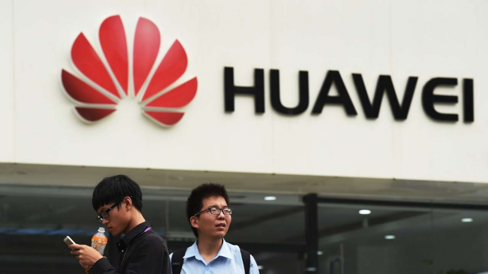 Two men stand in front of a Huawei store in Beijing, China
