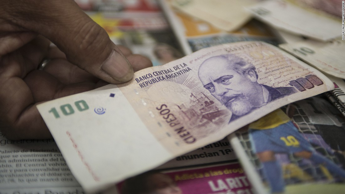Argentinian holding up the Argentina Peso, the country's currency
