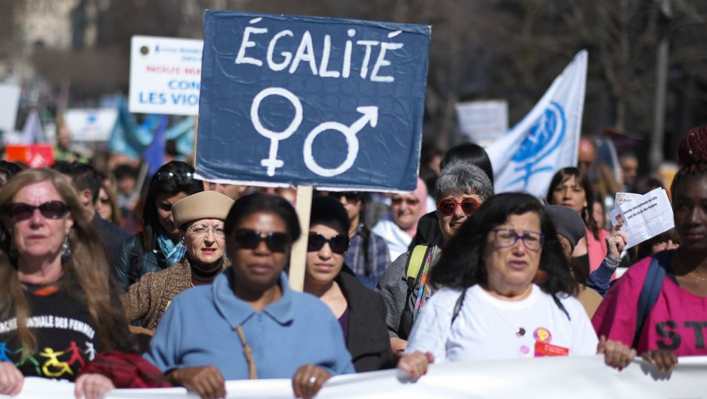 "A woman holds a banner reading ""Equality"" during an International Women's Day demonstration in the southern French city of Marseille"