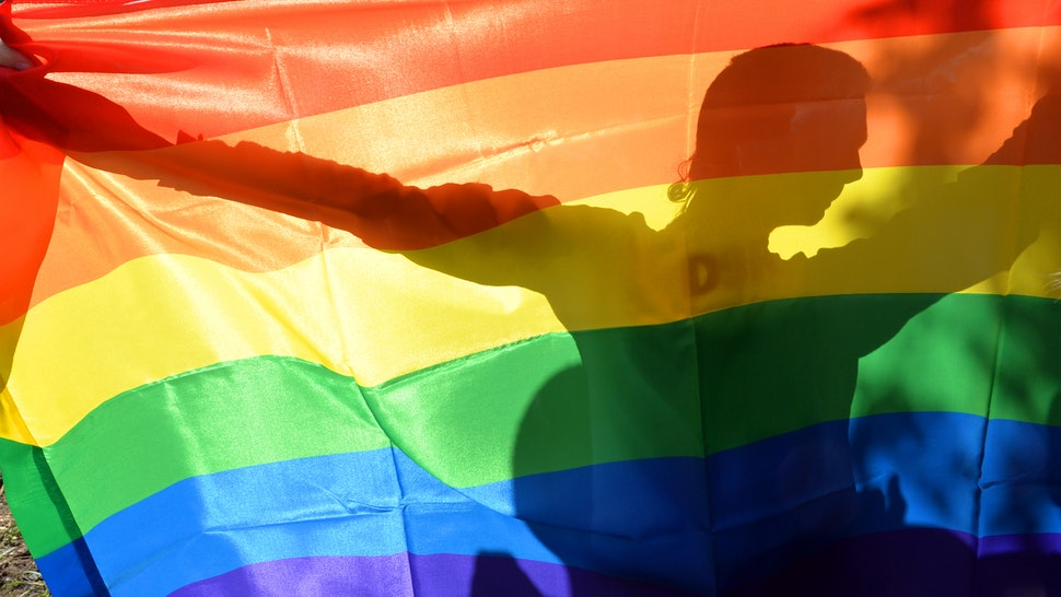 Man holding up a colored LGBT flag