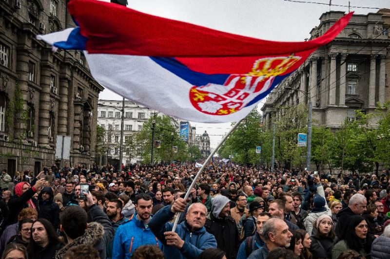 Protestors in Serbia waving a big flag above a crows
