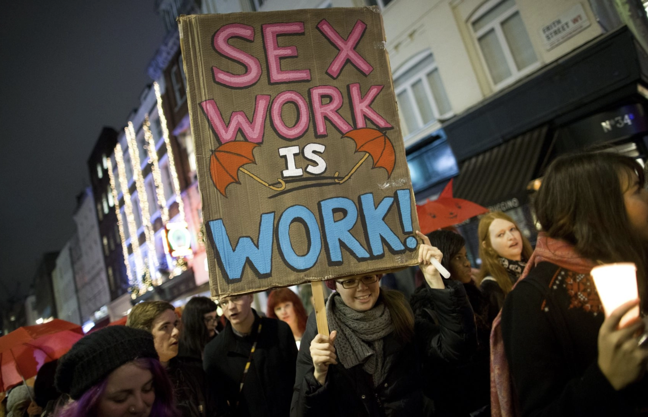 A protester holding a placard reading 'Sex work is work' while marching through Soho, NY, United States