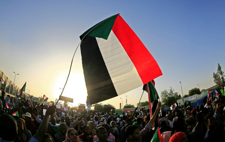 Protestors in Sudan wave a giant Sudanese flag above a crows of demonstrators