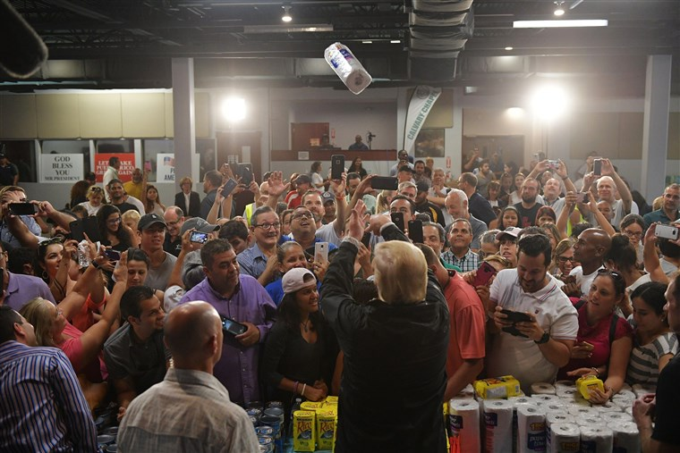 President Donald Trump throws rolls of paper towels into a crowd in Puerto Rico following Hurricane Maria