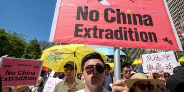 Man protesting in Hong Kong holding up a sign saying 'No China Extradition'