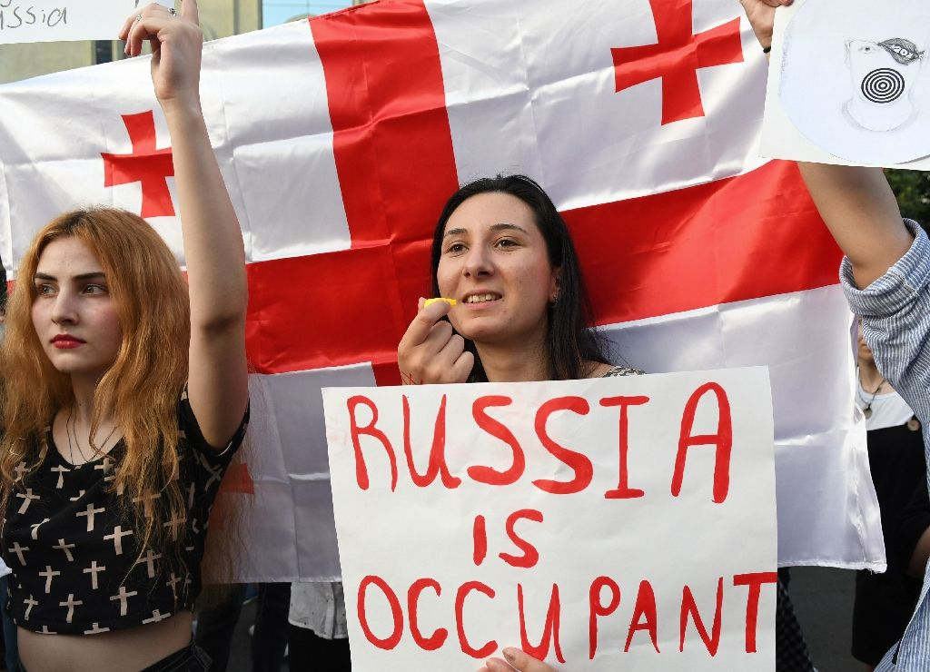 Women in front of a Georgian flag holds up a banner reading 'Russia is occupant'