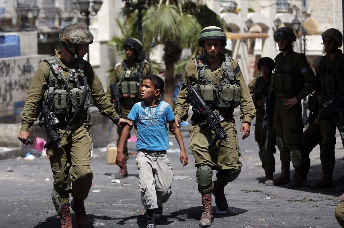 Israeli soldiers arrest a young Palestinian boy following clashes in the center of the West Bank town of Hebron, on June 20, 2014