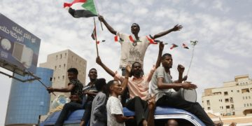 Protestors in Sudan wave a flag while sitting on top of a car
