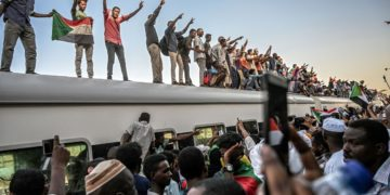 Sudanese protesters from the city of Atbara, flash the V-sign for victory and wave national flags atop a train, as it arrives at the Bahari station in Khartoum