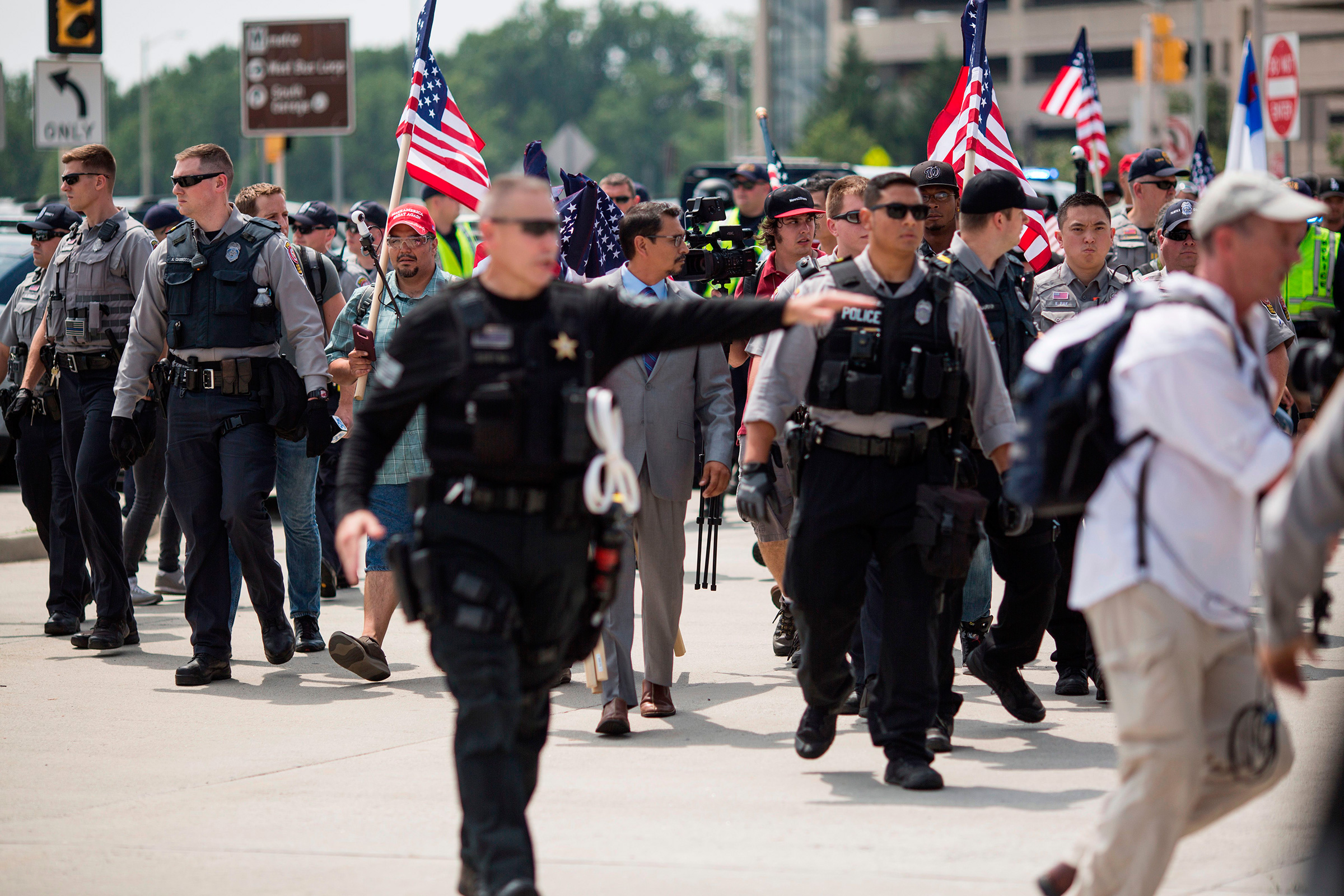 """Police escort demonstrators to the Vienna Metro Station ahead of the """"Unite the Right"""" rally August 12, 2018, in Vienna, Virginia"""