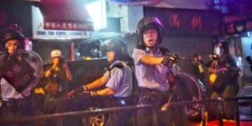 Police officers point their sidearms at protesters during violent clashes in Tseun Wan, Hong Kong