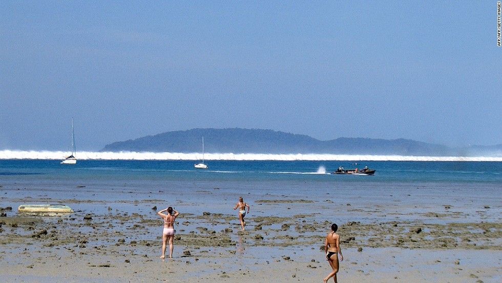 Water recedes as the first of six tsunami start to roll toward a beach in southern Thailand in 2004