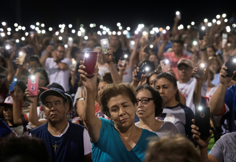 People hold up their phones during a prayer and candle vigil after a shooting left 21 people dead in El Paso, Texas