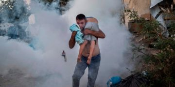 A man and a boy cry after police fire tear gas in a refugee camp in Lesbos (Greece). At least one woman and one child have died in a fire during riots with the police. Photo: Angelos Tzortzinis.