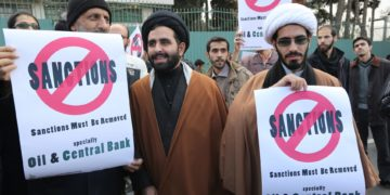 Iranian men hold placards reading 'Sanctions must be removed' in the capital Tehran on November 23, 2014