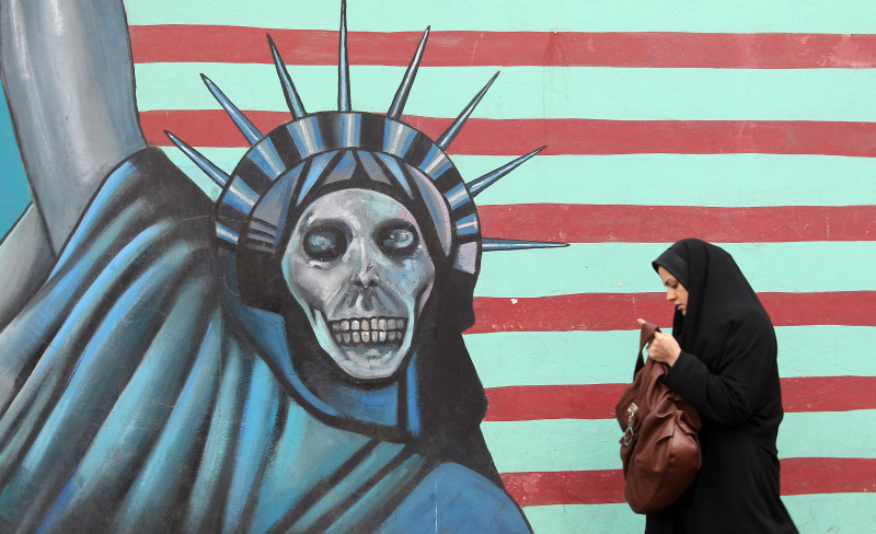 An Iranian woman walks past an anti-US mural painted on the wall of the former US embassy in Tehran on November 19, 2011
