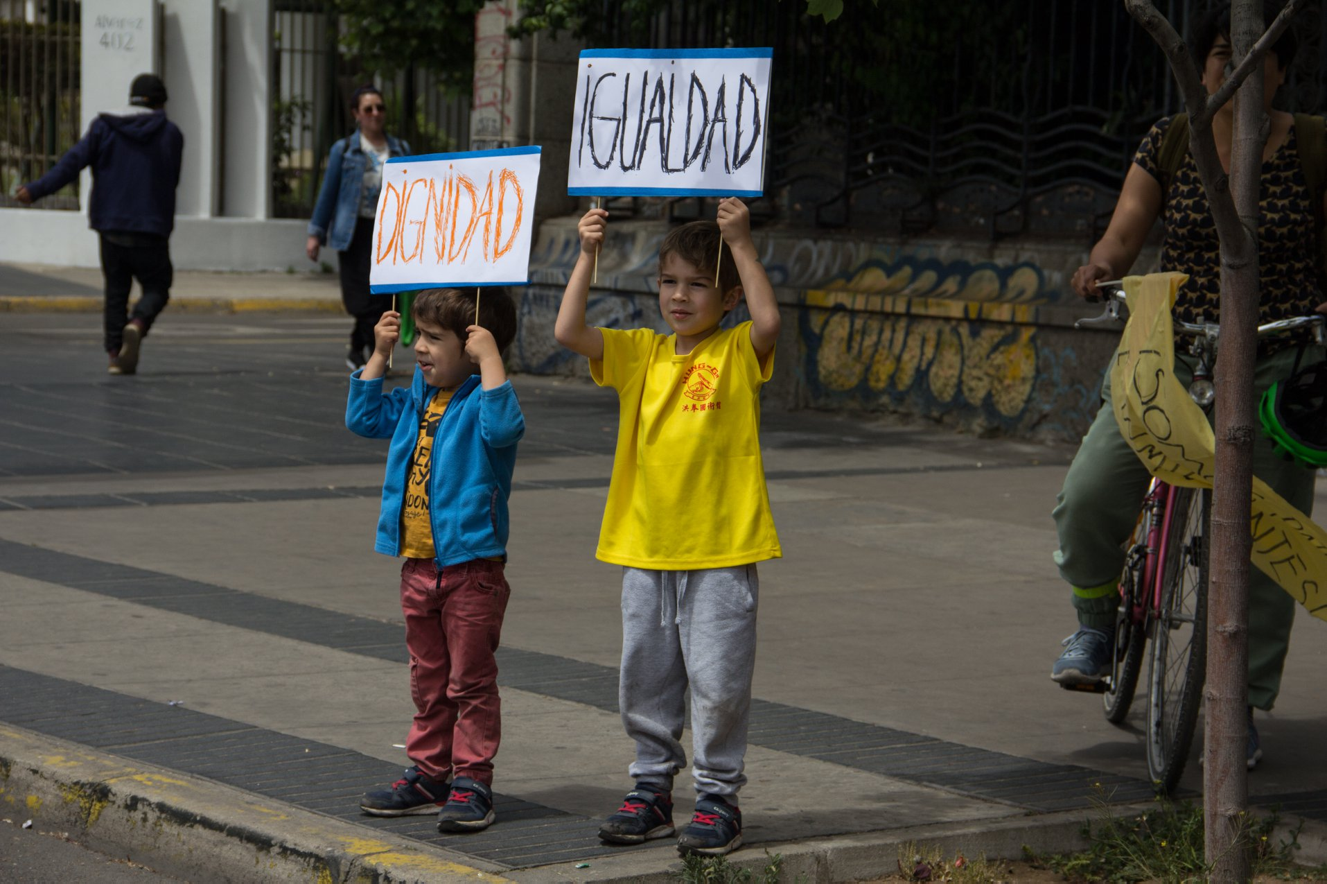 Two boys protest in Chile, holding up signs that read 'dignity' and 'equality.'