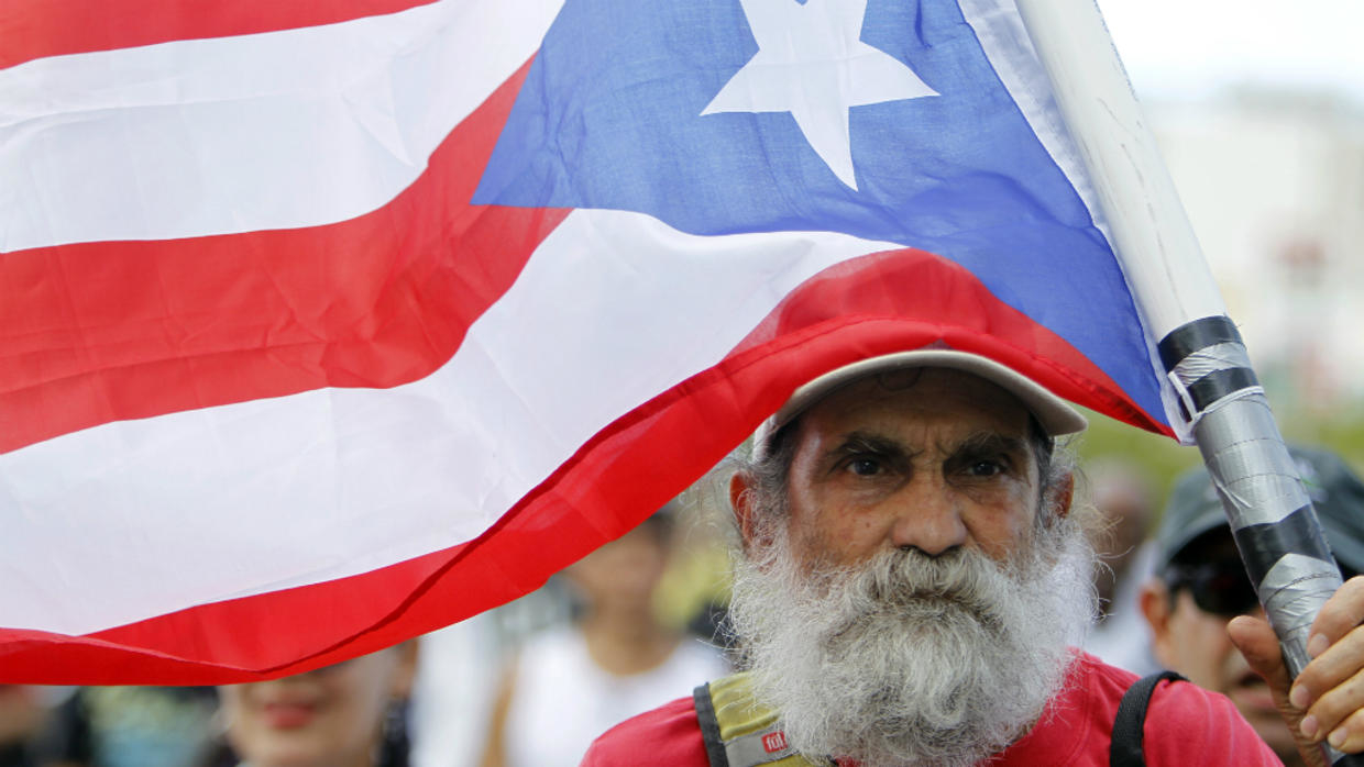 A man carries a Puerto Rican flag during a protest against the referendum for Puerto Rico political status in San Juan, on June 11, 2017.