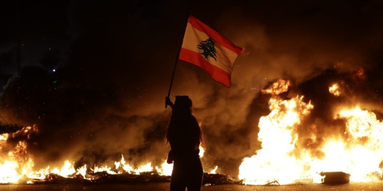 An anti-government protester waves a Lebanese flag in front of burning tires that block the main highway linking the cities of Tripoli and Beirut on Nov. 13, 2019