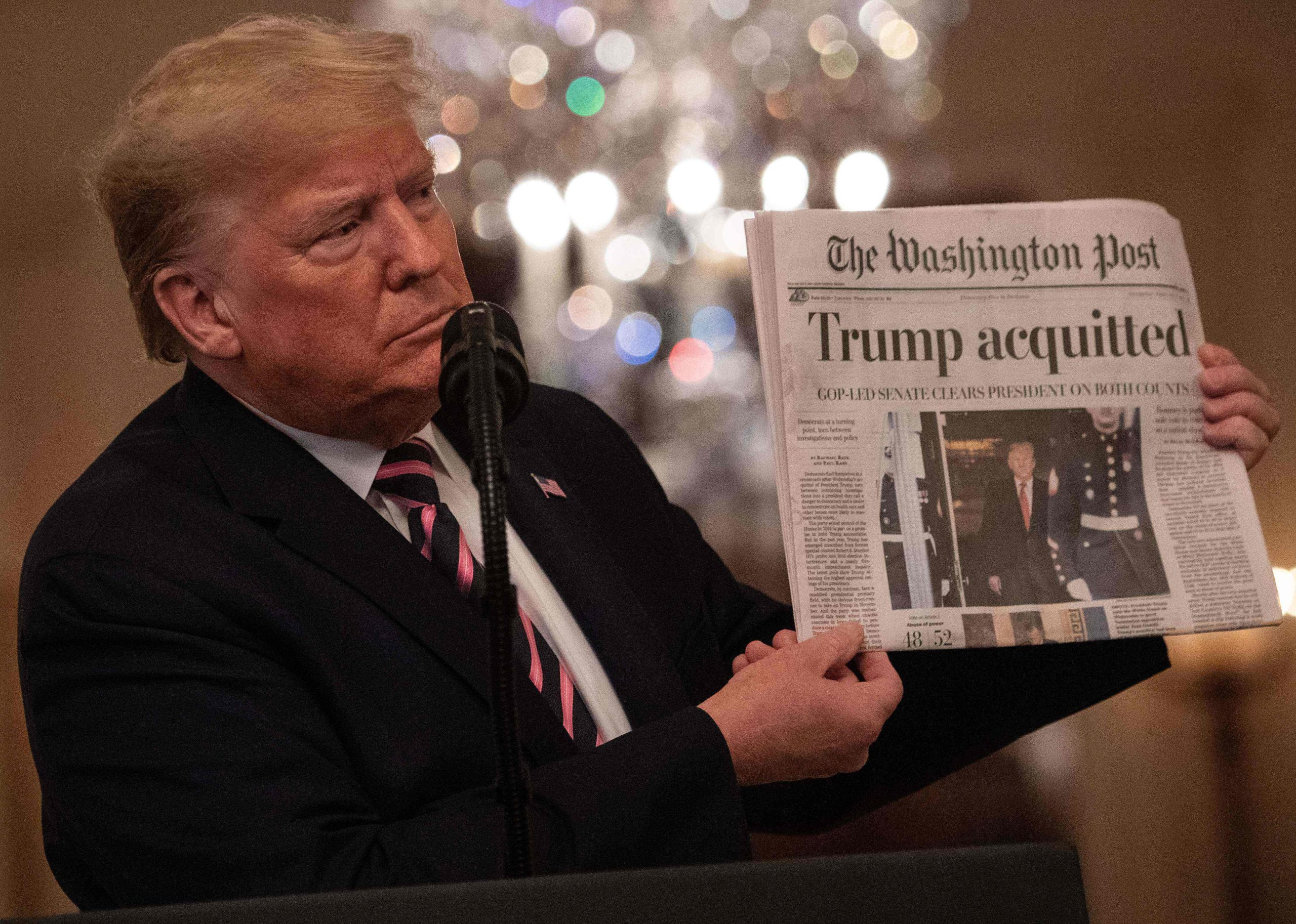 US President Donald Trump holding up The Washington Post that headlines 'Trump acquitted'