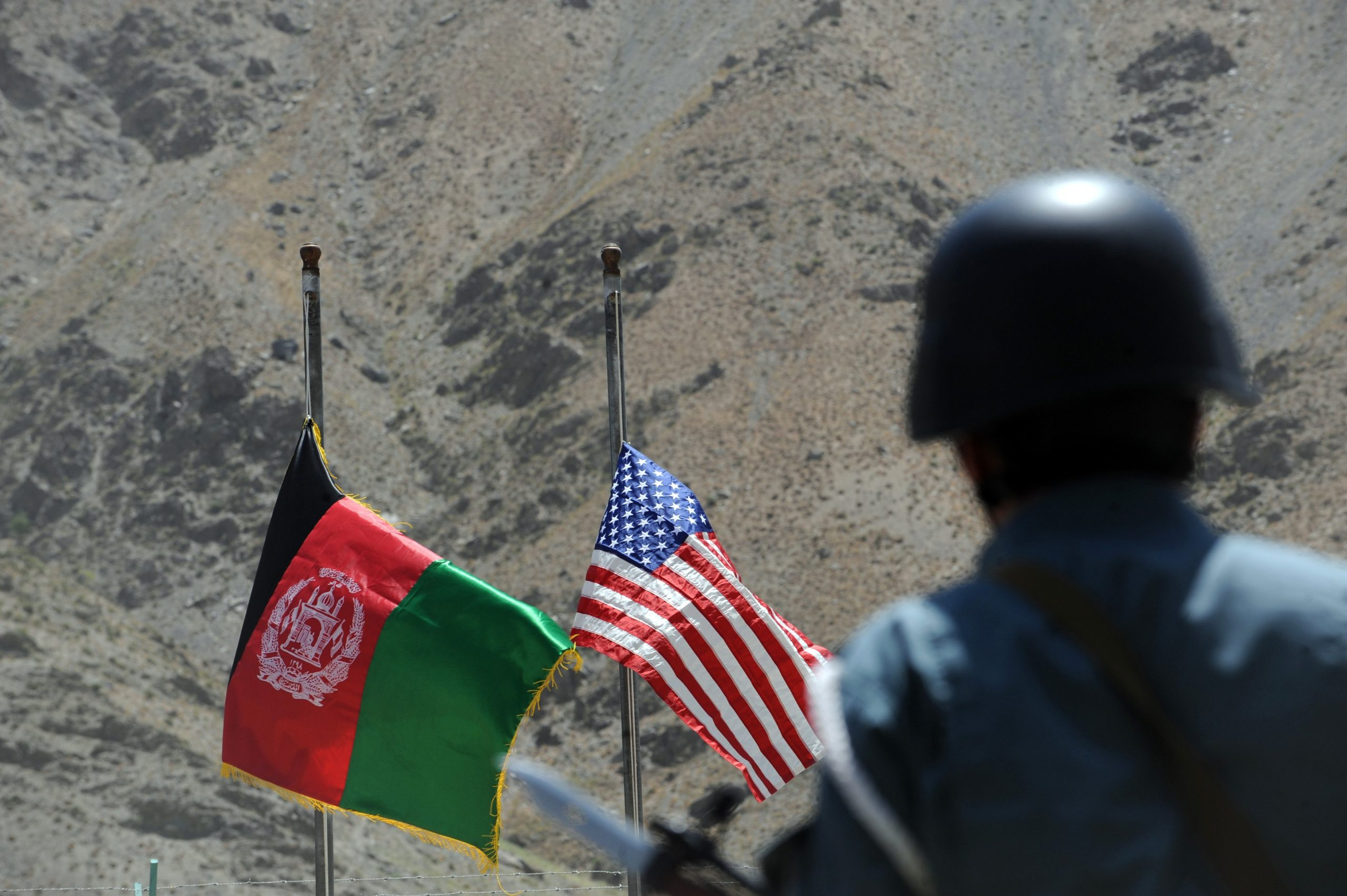 In this file photo taken on July 24, 2011 Afghan and US flags are raised as a policeman keeps watch during a ceremony to hand over security control in the rugged mountains of the Panjshir valley.