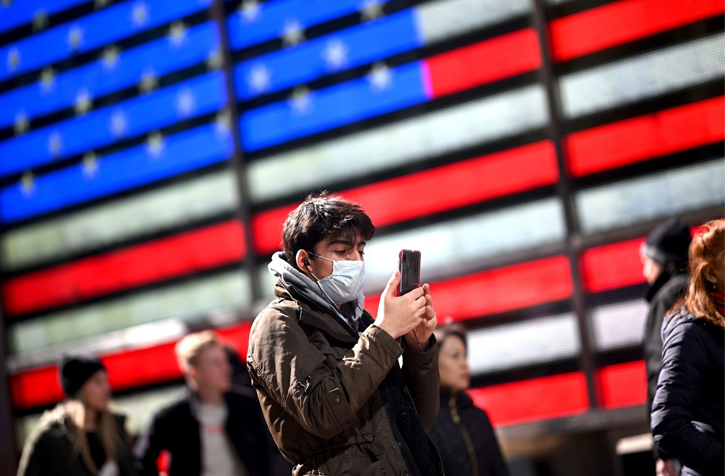 A man wears a mask as uses his cellphone at Times Square in front of an American flag on March 5, 2020, in New York City