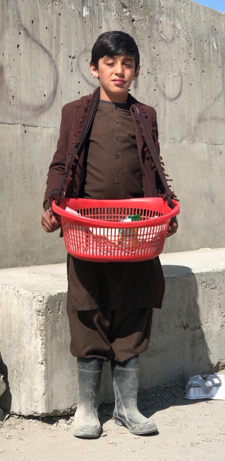 11-year-old Afghan boy Farhad showing his basket of eggs.