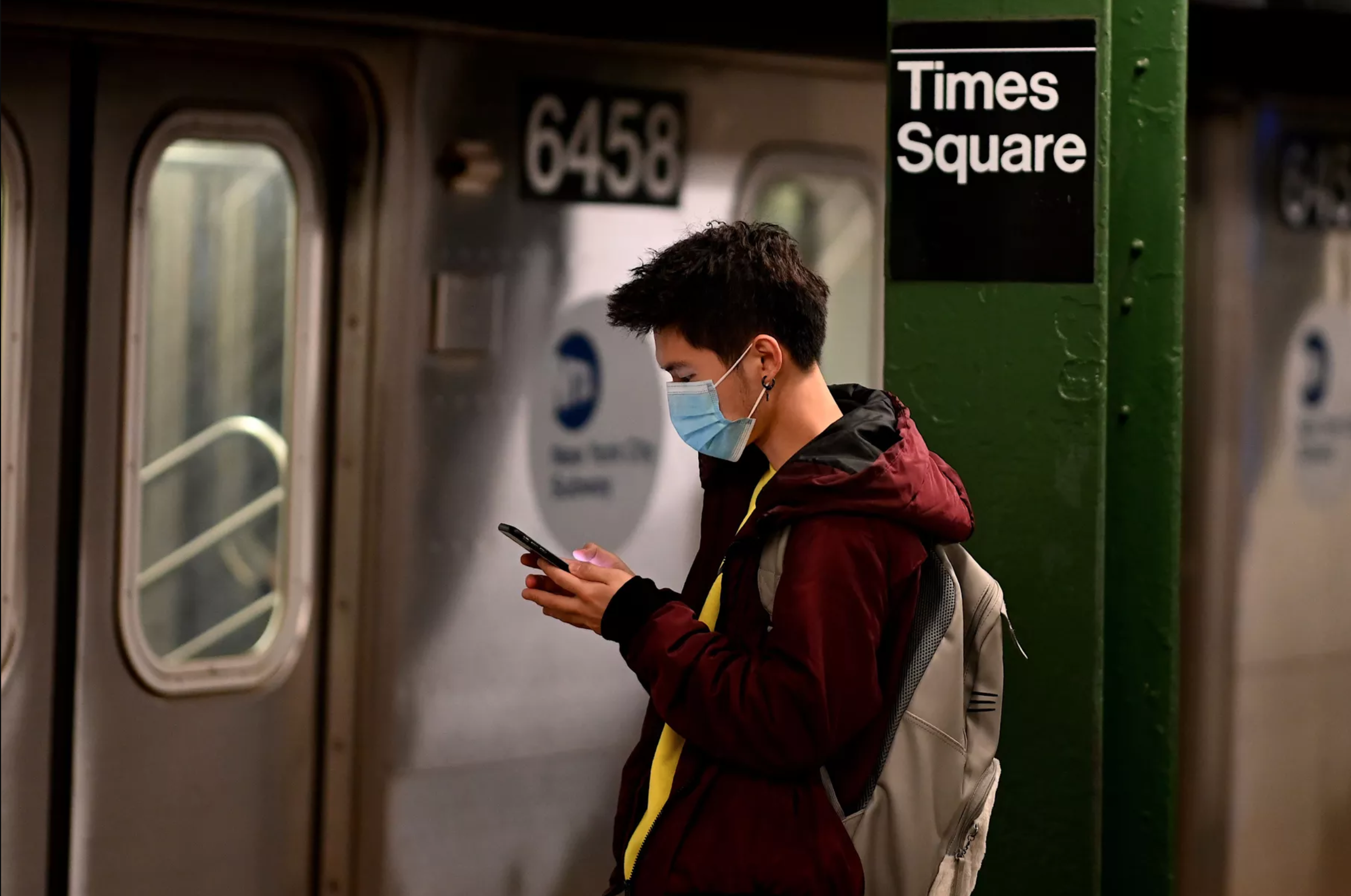 A man wearing a face mask looks at his phone in the New York metro during the coronavirus outbreak.