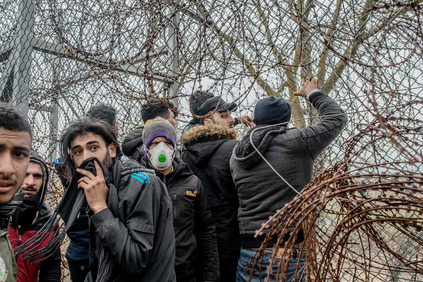 Migrants try to get through border fencing between Turkey and Greece.