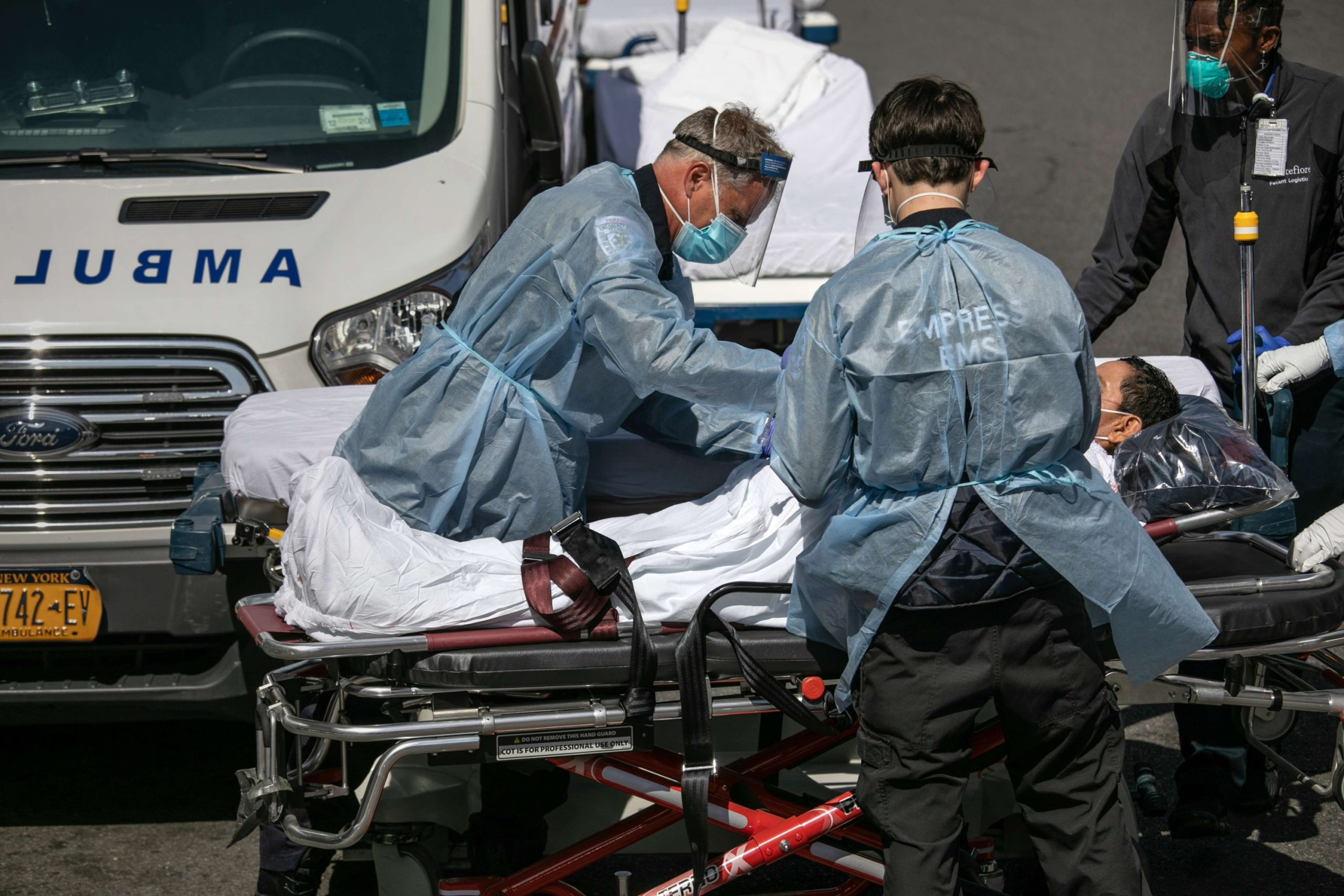 Medics and hospital workers tend to a COVID-19 patient outside the Montefiore Medical Center Moses Campus in the Bronx, New York City.