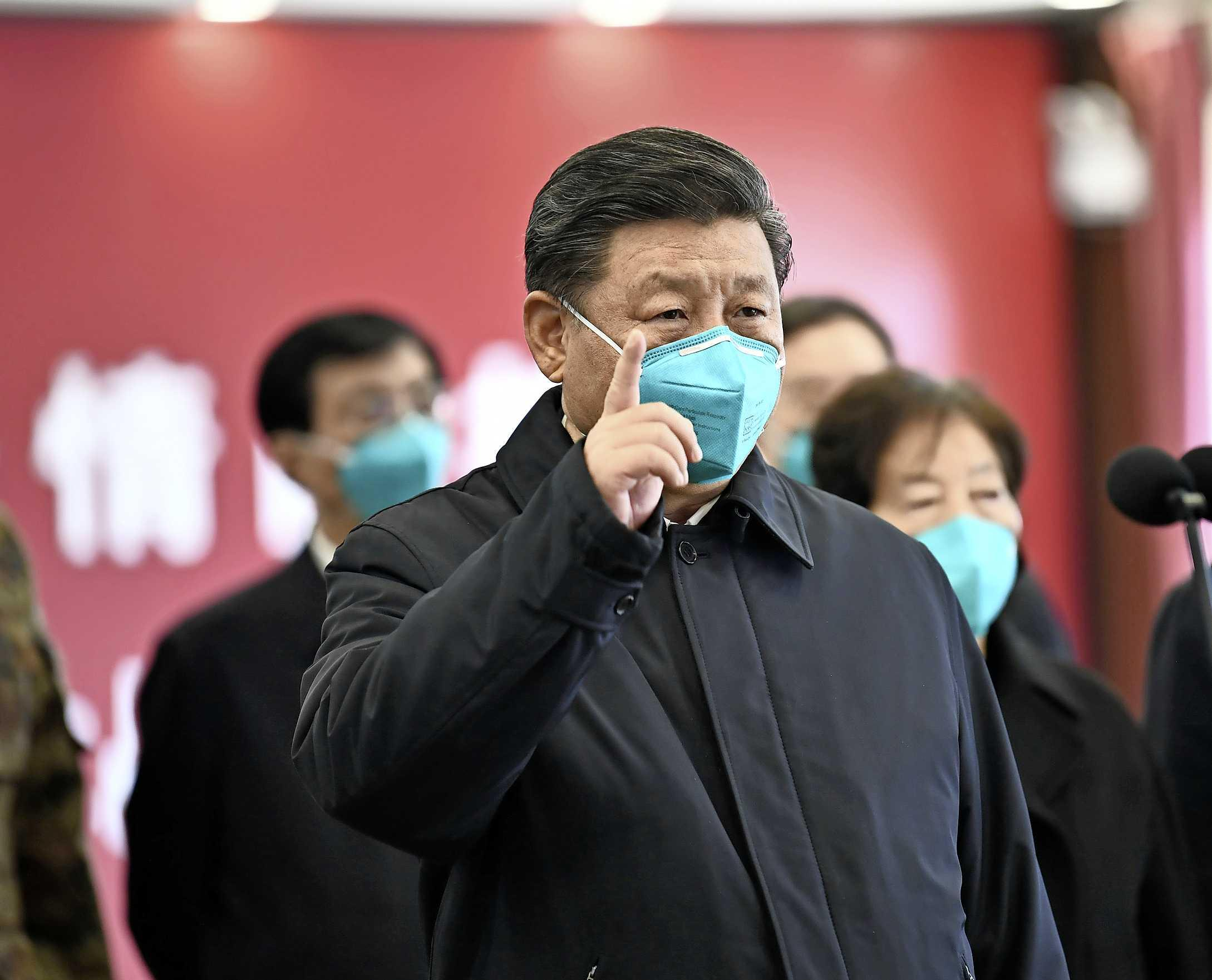 Chinese President Xi Jinping wearing a mask as he gestures to a coronavirus patient and medical staff via a video link at the Huoshenshan hospital in Wuhan, in China's central Hubei province on March 10, 2020