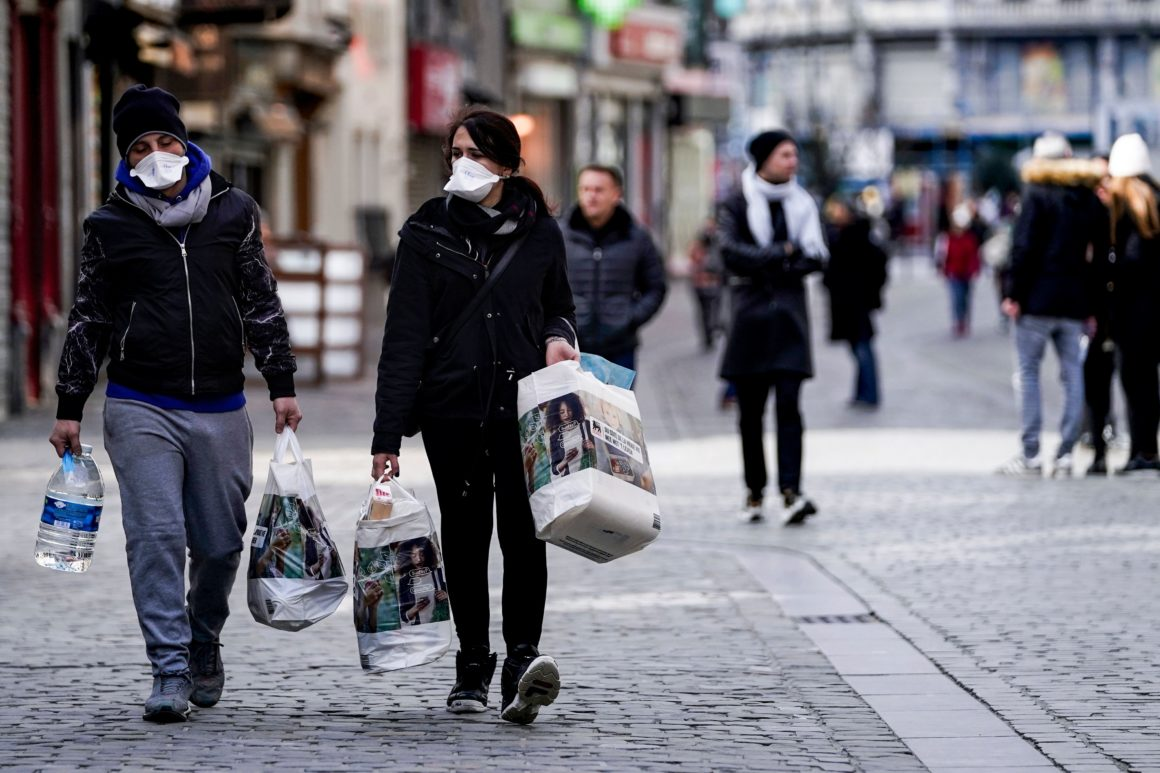 People wear protective face masks as they carry groceries in the centre of Brussels, amid the outbreak of COVID-19, caused by the novel coronavirus