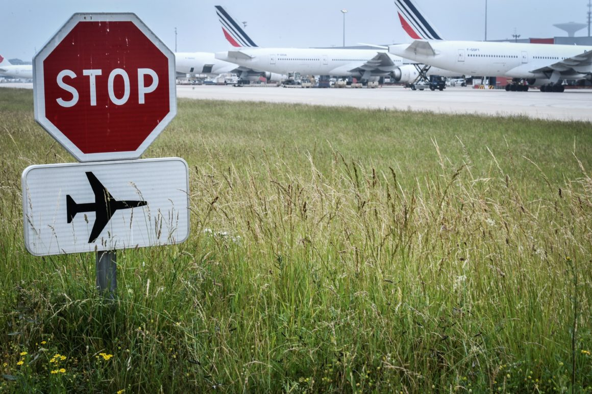 Stop sign and (in the background) Air France company's planes parked at Roissy Charles de Gaulle airport, north of Paris.