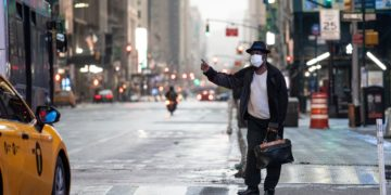 A man wearing a mask tries to catch a taxi at Times Square amid the COVID-19 pandemic on April 30, 2020 in New York City