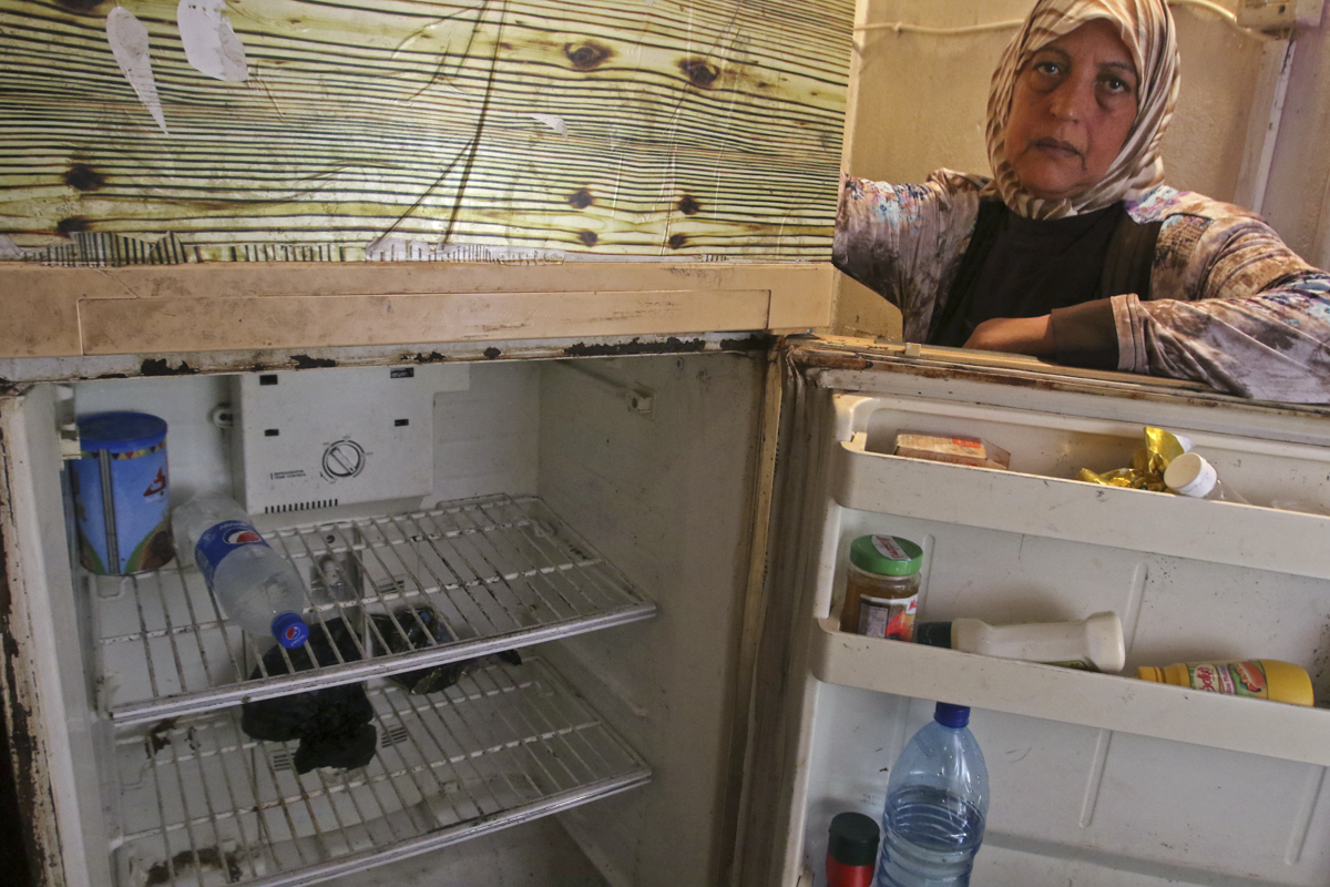 Lebanese woman opening empty refrigerator in the southern city of Sidon on June 16, 2020.