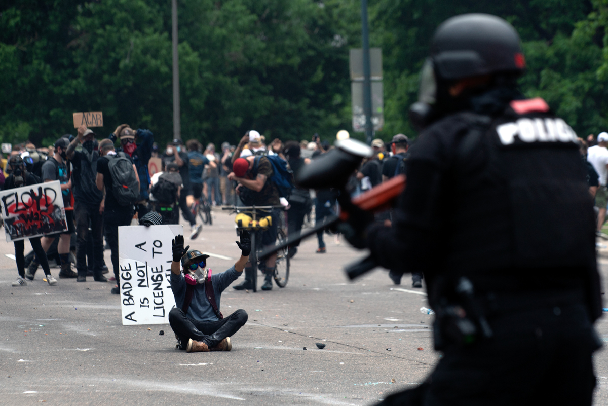 A demonstrator raises his arms up while facing off with police officers during a protest in Colorado in May 2020