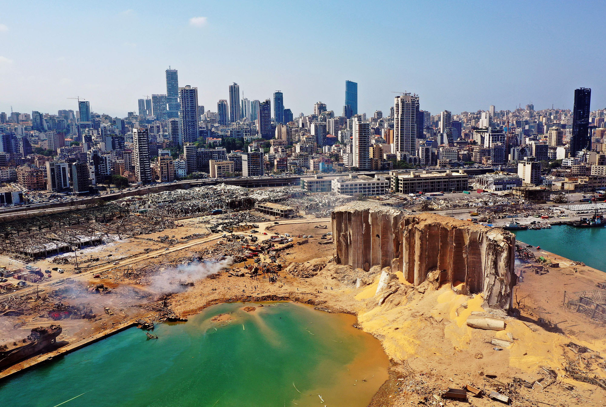 An aerial view of the Beirut port after the explosion. The blast created a 140 meter (460 feet) wide crater that has since filled with sea water. Photo: AFP.
