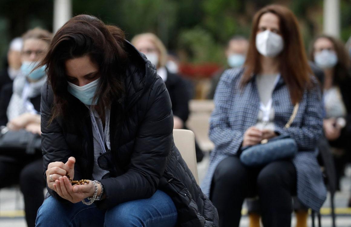 People praying in face masks