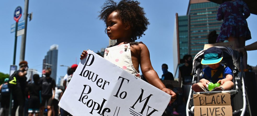 A child holds a poster during a Black Lives Matter rally.