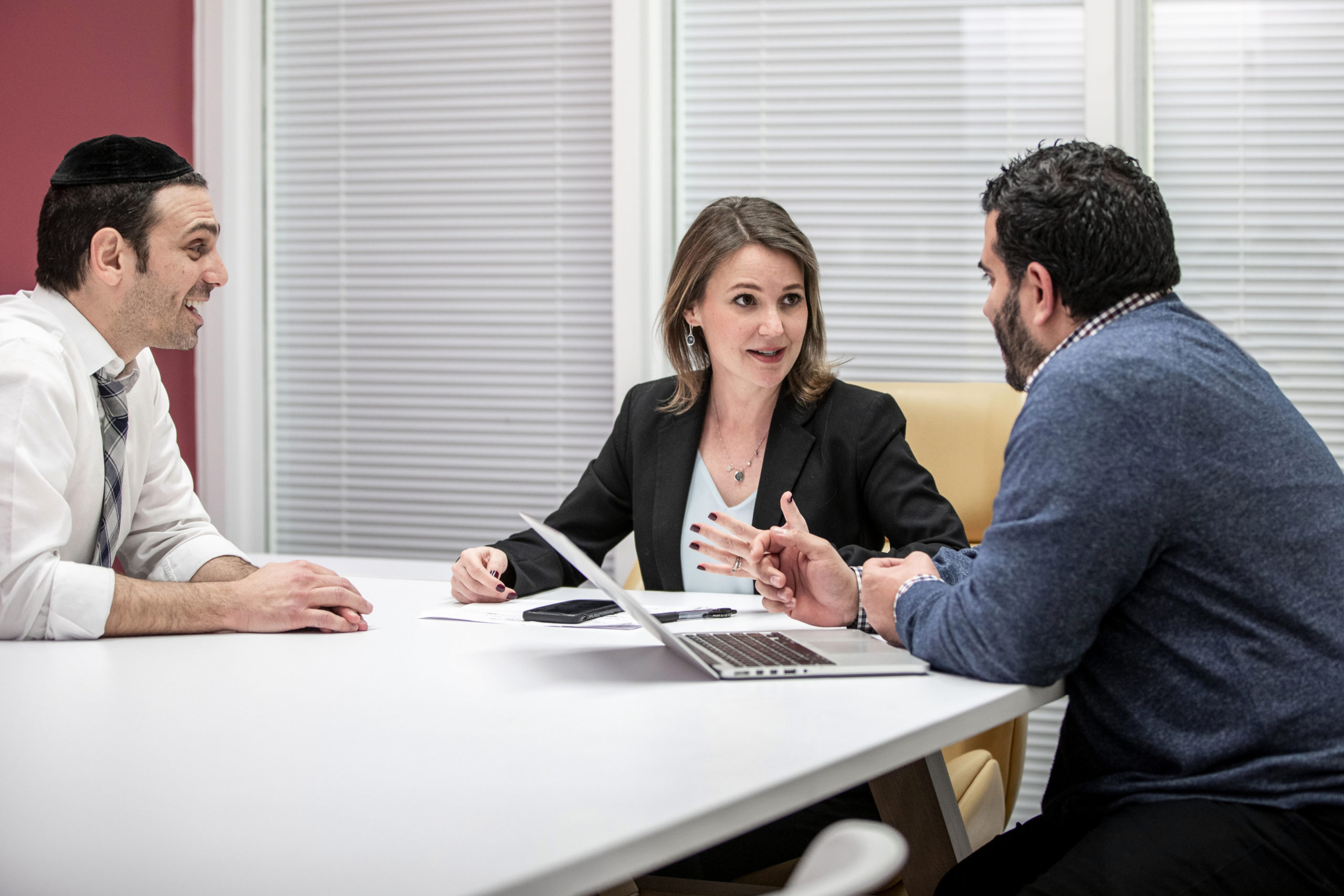 A woman talks to her colleagues in the boardroom