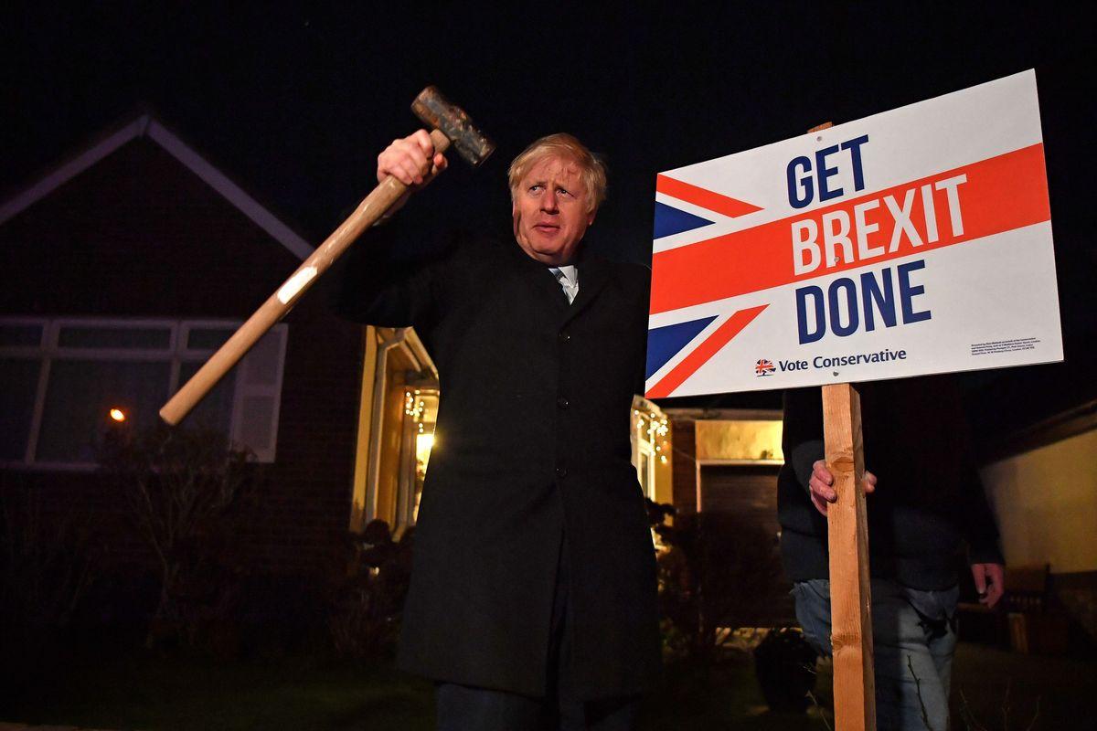 "Boris Johnson hammers a ""Get Brexit Done"" sign. Photo: Ben"