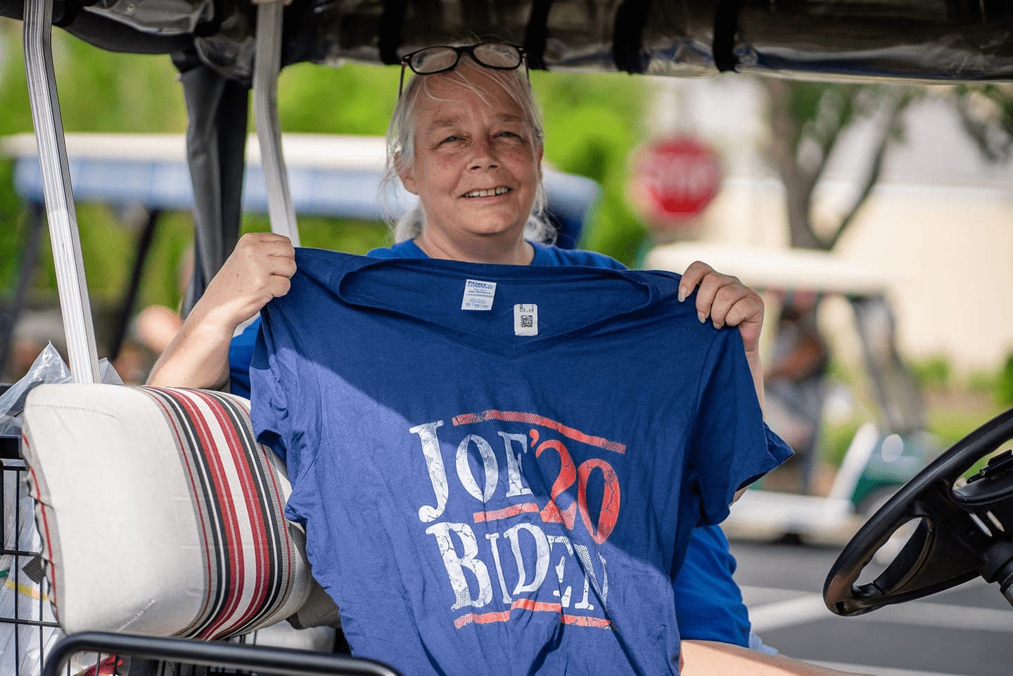 "Chris Stanley holding a blue t-shirt that reads ""Joe Biden '20"""