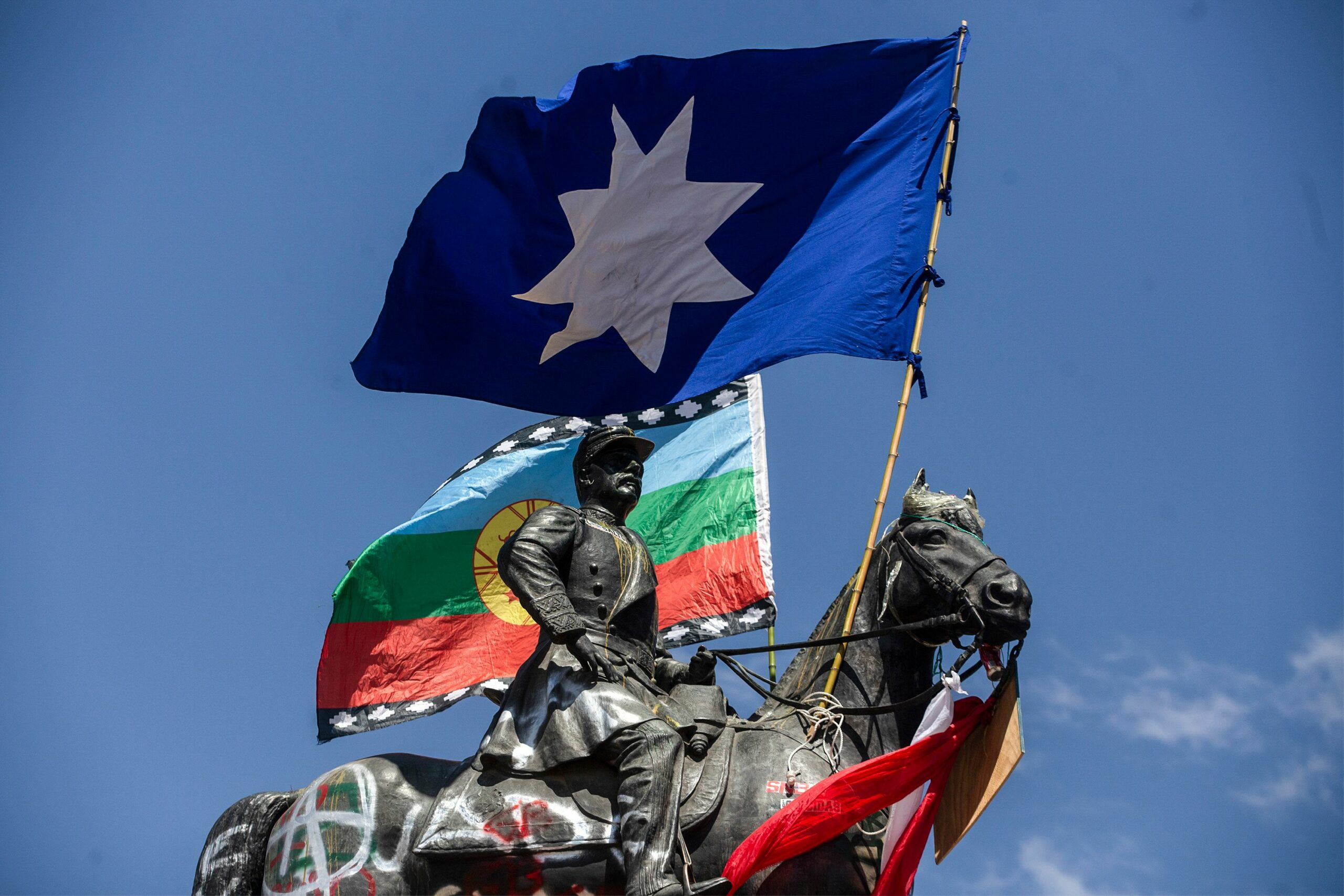 Statue with Mapuche flags
