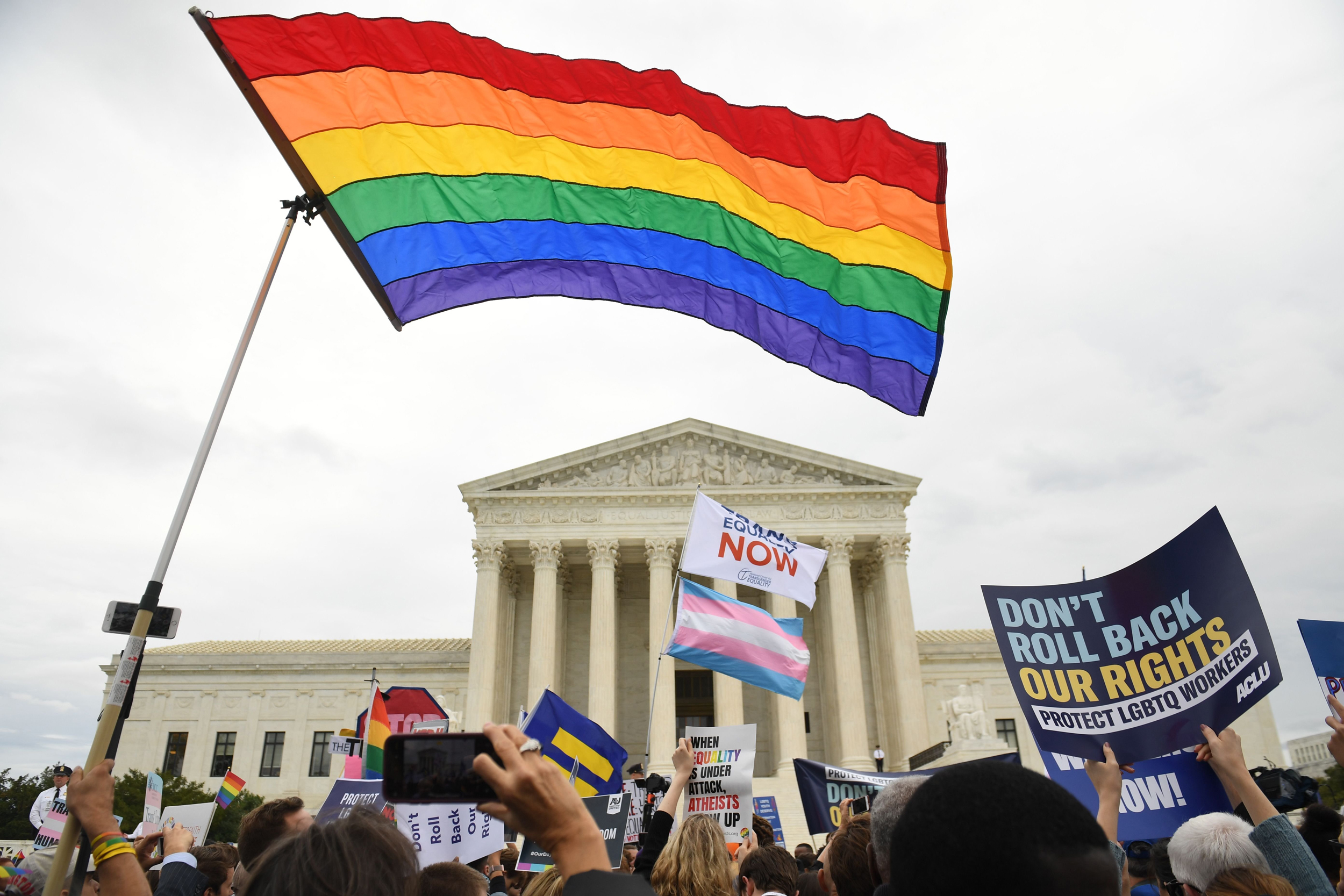 People holding LGBTQ signs outside the US Supreme Court
